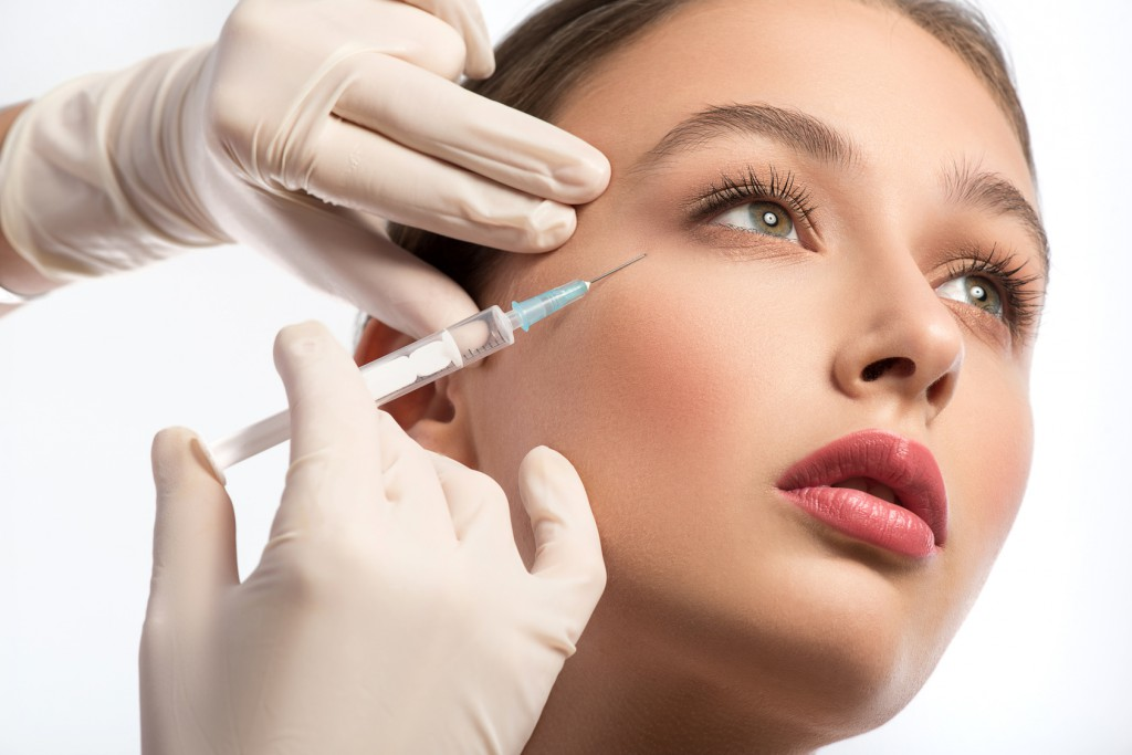 Serine young woman is getting facial botox injection. Beautician hands in gloves holding syringe near her face